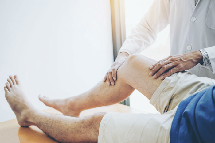 A doctor consulting with Detroin man with knee pain