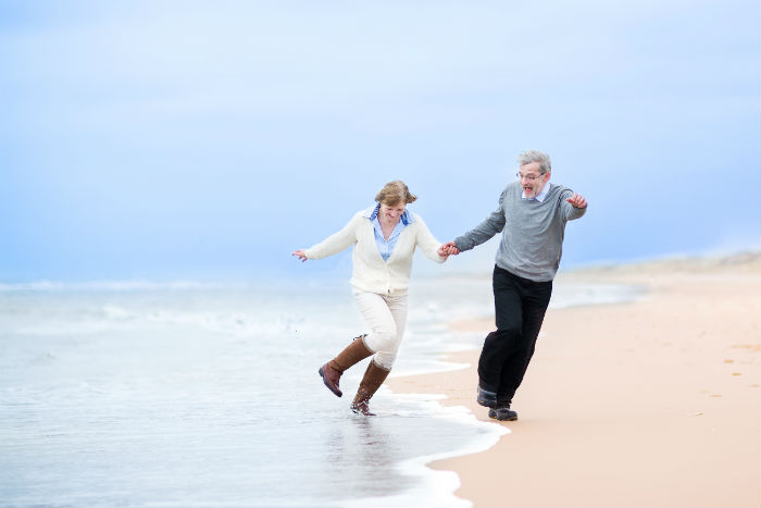 An elderly couple happily walk on Anchorage beach