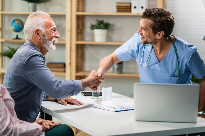 A senior man shakes the stem cell doctor's hand